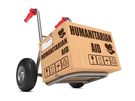 Humanitarian Aid Slogan on Cardboard Box on Hand Truck White Background.