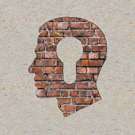 Profile of Head with a Keyhole Icon on the Brick and Plastered Wall. photo