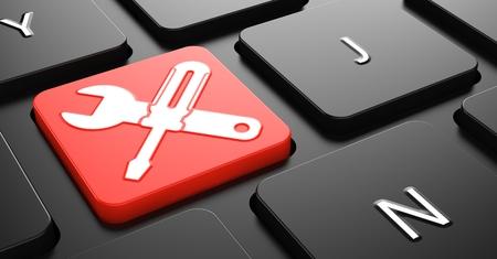 Gekruiste schroevendraaier en moersleutel op de rode knop op zwart toetsenbord.