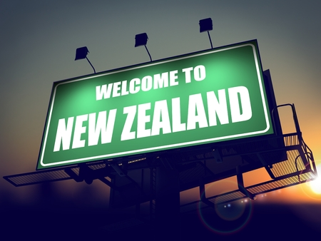 Welcome to New Zealand - Green Billboard on the Rising Sun Background. photo