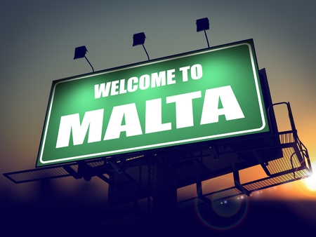 Welcome to Malta - Green Billboard on the Rising Sun Background. photo