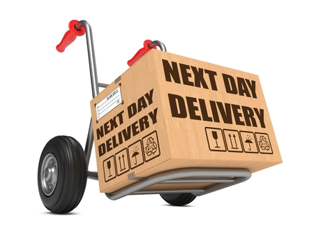 Cardboard Box with Next Day Delivery Slogan on Hand Truck White Background. Stock Photo