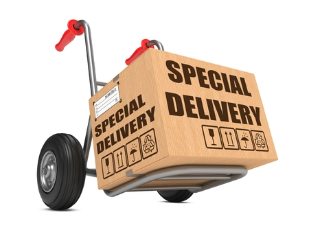 Cardboard Box with Special Delivery Slogan on Hand Truck White Background. photo