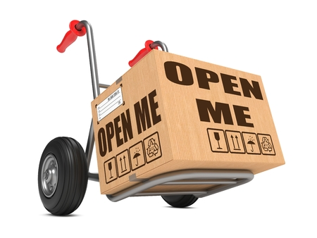 Cardboard Box with Open Me Slogan on Hand Truck Isolated on White.