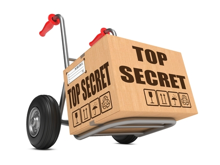 millboard: Cardboard Box with Top Secret Slogan on Hand Truck Isolated on White. Stock Photo