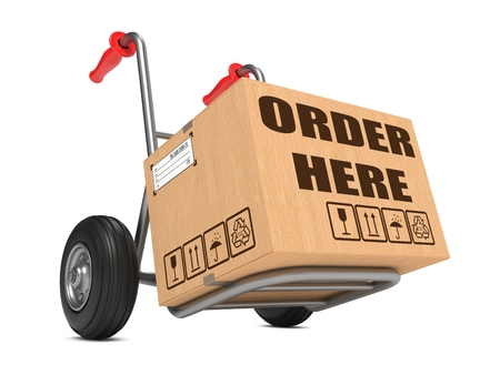 order here: Cardboard Box with Order Here Slogan on Hand Truck Isolated on White. Stock Photo