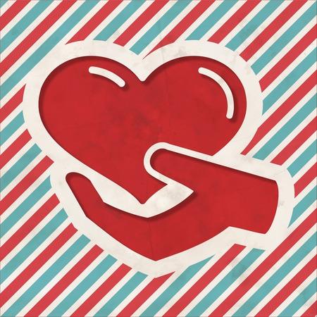 generoso: Concepto Caridad - Icono del Corazón en la Mano en fondo rojo y azul de rayas. Concepto de la vendimia en diseño plano.