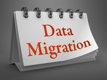 Data Migration - Red Words on White Desktop Calendar Isolated on Gray Background. photo