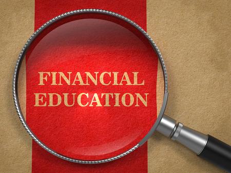 Concepto de la educación financiera. Lupa en el papel viejo con el fondo de la línea roja vertical.