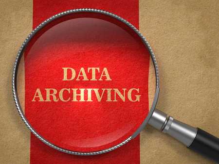 archiving: Data Archiving concept. Magnifying Glass on Old Paper with Red Vertical Line Background. Stock Photo