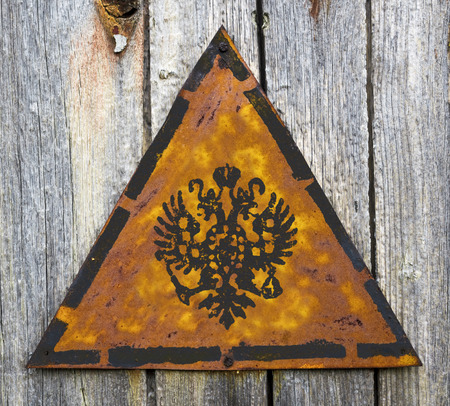 grange: Double Eagle - Russian Coat of Arms on Weathered Triangular Yellow Warning Sign. Grange Background.