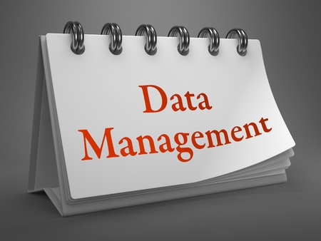Data Management - Red Words on White Desktop Calendar Isolated on Gray Background. photo