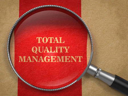 TQM -  Total Quality Management Concept. Magnifying Glass on Old Paper with Red Vertical Line Background. photo