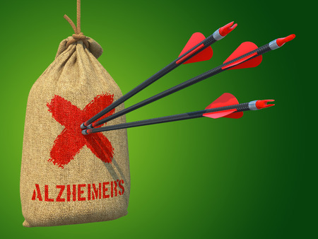 aging brain: Alzheimers - Three Arrows Hit in Red Mark Target on a Hanging Sack on Green Background  Stock Photo