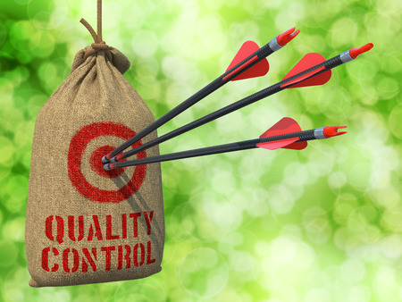 Quality Control - Three Arrows Hit in Red Target on a Hanging Sack on Green Bokeh Background  photo