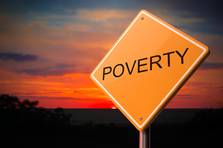 Poverty on Warning Road Sign on Sunset Sky Background. Stock Photo