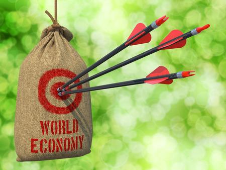 labor relations: Econom�a Mundial - Tres flechas dieron en Red Target en un saco que cuelga en el fondo verde de Bokeh. Foto de archivo