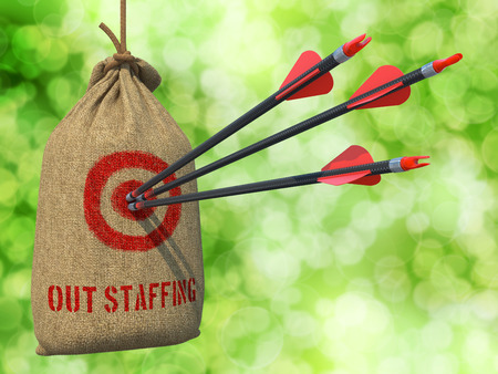 minimization: Outstaffing - Three Arrows Hit in Red Target on a Hanging Sack on Green Bokeh Background. Stock Photo