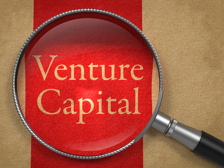 capitalist: Venture Capital through Magnifying Glass on Old Paper with Red Vertical Line.