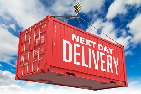 Next Day Delivery - Red Cargo Container hoisted with hook on Blue Sky Background. photo
