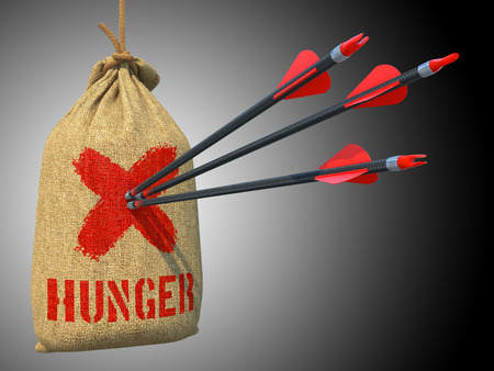 dearth: Hunger - Three Arrows Hit in Red Target on a Hanging Sack on Green Bokeh Background. Stock Photo