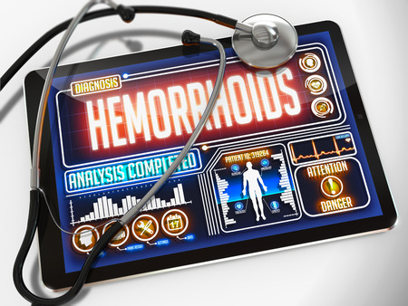 hemorrhoids: Medical Tablet with the Diagnosis of Hemorrhoids on the Display and a Black Stethoscope on White Background.