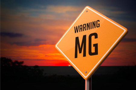 nicotinic: MG on Warning Road Sign on Sunset Sky Background. Stock Photo