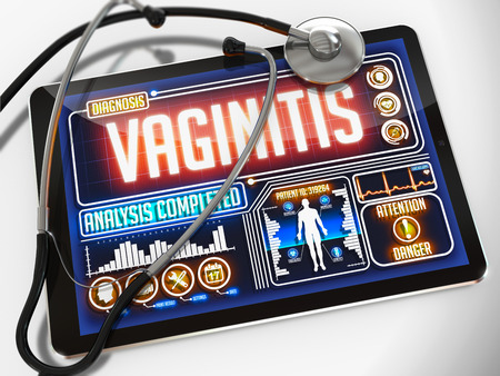 Medical Tablet with the Diagnosis of Vaginitis on the Display and a Black Stethoscope on White Background. photo
