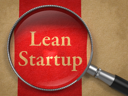 founding: Lean Startup through a Magnifying Glass on Old Paper with Red Line.