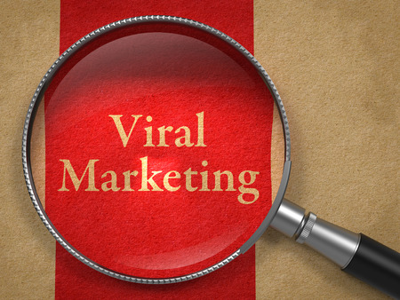 Viral Marketing through Magnifying Glass on Old Paper with Red Vertical Line. photo