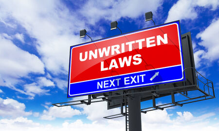 constraint: Unwritten Laws Inscription on Red Billboard on Sky Background. Stock Photo