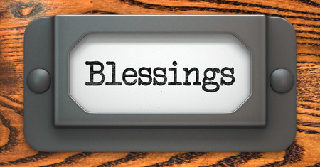 Blessing Inscription on File Drawer Label on a Wooden Background.