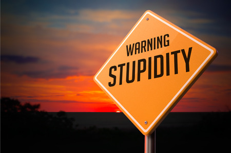 irrelevant: Stupidity on Warning Road Sign on Sunset Sky Background.
