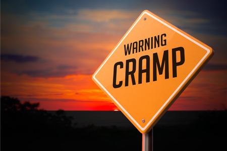 cramp: Cramp on Warning Road Sign on Sunset Sky Background. Stock Photo