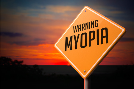 Myopia on Warning Road Sign on Sunset Sky Background. Stock Photo