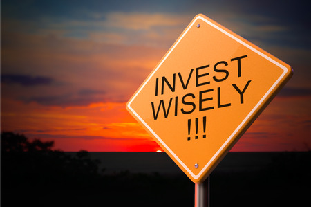 company ownership: Invest Wisely on Warning Road Sign on Sunset Sky Background. Stock Photo