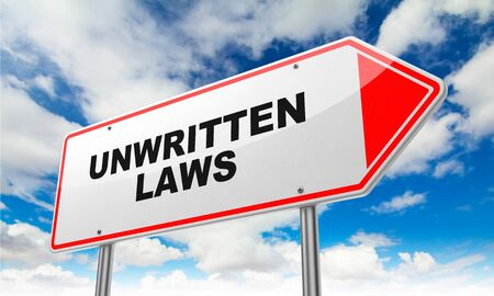 behavioral: Unwritten Laws on Red Road Sign on Sky Background. Stock Photo