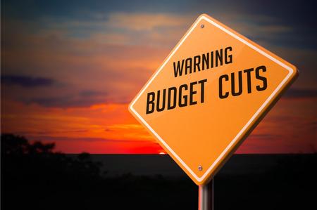 minimization: Budget Cuts on Warning Road Sign on Sunset Sky Background.
