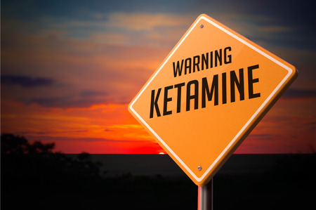 hallucinogen: Ketamine on Warning Road Sign on Sunset Sky Background.