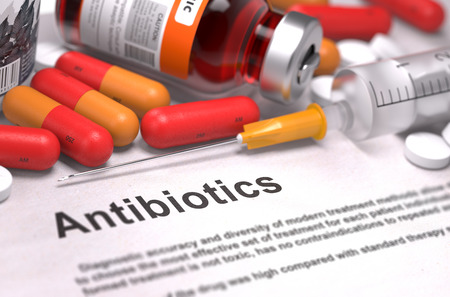 antimicrobial: Antibiotics - Printed Diagnosis with Blurred Text. On Background of Medicaments Composition - Red Pills, Injections and Syringe. Stock Photo