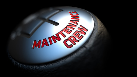 qualitatively: Maintenance Crew - Red Text on Black Gear Shifter with Leather Cover. Close Up View. Selective Focus.
