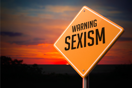sex discrimination: Sexism on Warning Road Sign on Sunset Sky Background. Stock Photo