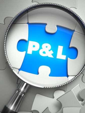 Profit and Loss - Word on the Place of Missing Puzzle Piece through Magnifier. Selective Focus.