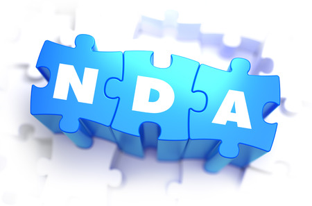 NDA - Non Disclosure Agreement - Text on Blue Puzzles on White Background. 3D Render. Stock Photo