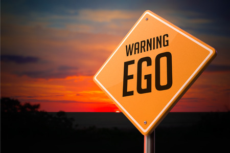 narcissism: EGO on Warning Road Sign on Sunset Sky Background.