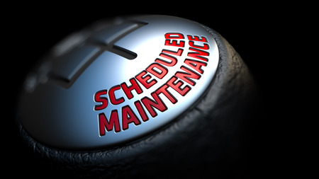 scheduled: Scheduled Maintenance - Red Text on Black Gear Shifter with Leather Cover. Close Up View. Selective Focus. Stock Photo