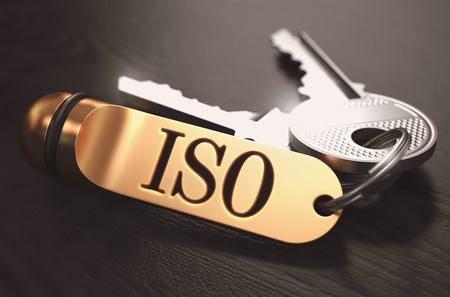 standardization: ISO - International Organization for Standardization - Concept. Keys with Golden Keyring on Black Wooden Table. Closeup View, Selective Focus, 3D Render. Toned Image.
