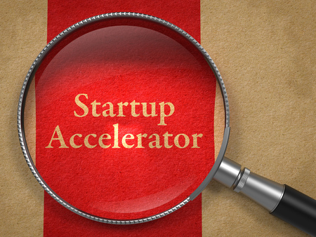 accelerator: Startup Accelerator through Magnifying Glass on Old Paper with Red Vertical Line. Stock Photo
