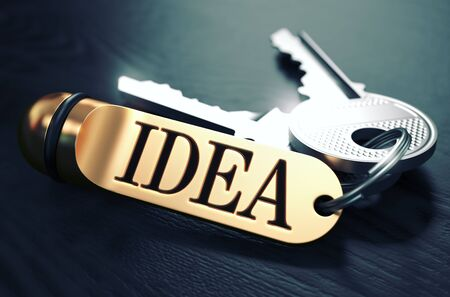 suddenness: Keys and Golden Keyring with the word Idea over Black Wooden Table with Blur Effect. Toned Image. Stock Photo