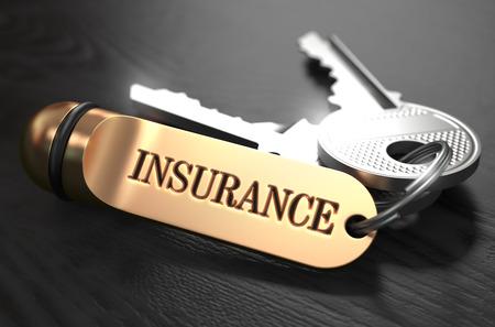 Toetsen en Gouden Sleutelhanger met het Woord Insurance over Zwarte houten tafel met Blur Effect.